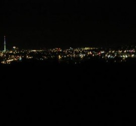 The lights of the city beyond the darkness of West Auckland